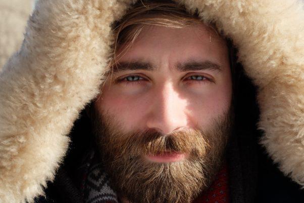 Closeup of a bearded man's face wearing a parka hood. (Photo: Frank Marino/Unsplash)