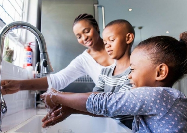 An African American mother, her young son and daughter washing their hands at the kitchen sink. (Photo: Getty Images)