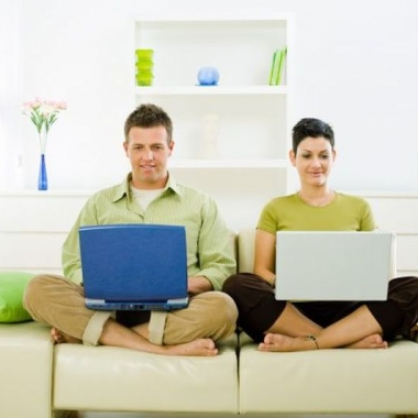 Man and woman working side-by-side on laptops while sitting on a white couch. (Photo: Shutterstock)