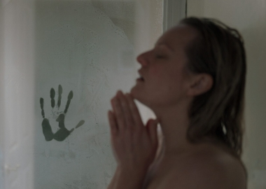 A handprint in the steam on the door as Cecilia Kass (Elizabeth Moss) takes a hot shower. (Photo: Univesal Pictures)