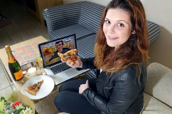 A man and woman eating pizza together while having a video date. (Photo: Press Eye)