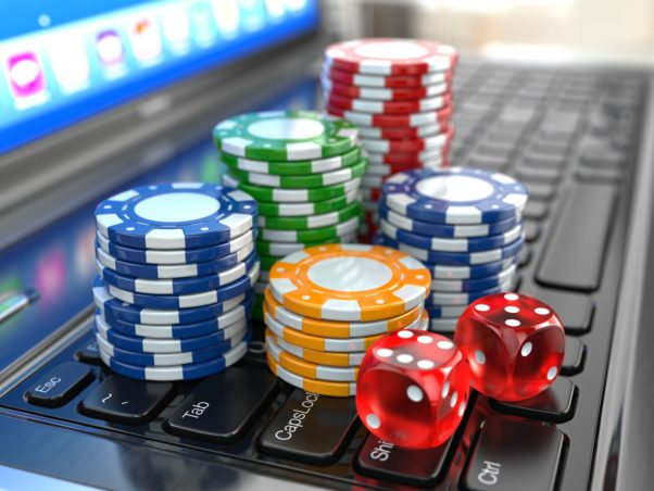Green, blue, red and yellow poker chips and two red dice sittig on a laptop keyboard. (Photo: Shutterstock)