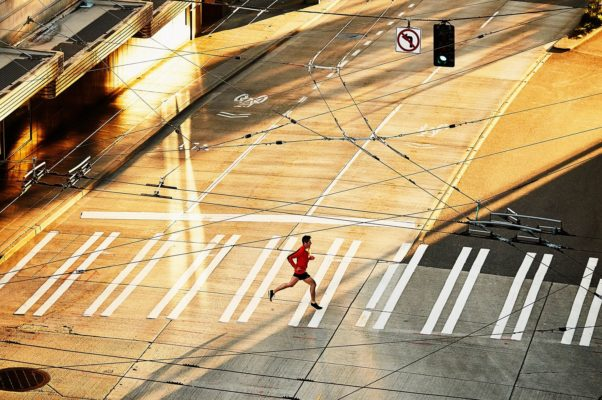 A lone runner crossing a deserted street. (Photo: Getty Images)