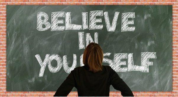 "Woman facing a blackboard that reads ""BELIEVE IN YOURSELF."" (Photo: Gerd Altmann/Pixabay)"
