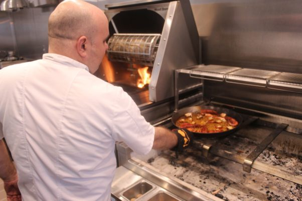 Chef Danny Lledó cooks paella in Xiquet's glass-enclosed kitchen. (Photo: Mark Heckathorn/DC on Heels)