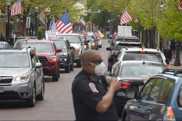 Vehicles with flags and signs fill Church Circle in Annapolis as a police officer directs traffic. (Photo: Brian Krista/Capital Gazette)
