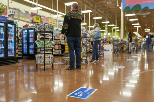 "Customers standing in a checkout line at a Kroger store with a signs on the floor that read ""Please Wait Here."" (Photo: Kroger)"