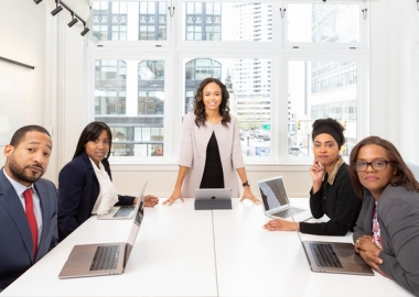 Woman standing in the center in a blazer with four people sitting around the table with laptops. (Photo: Rebrand City/Pexels)