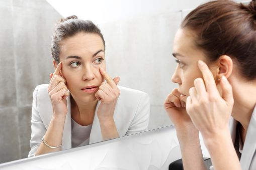 Woman looking at dark circles under her eyes in a mirror. (Photo: Vichy)