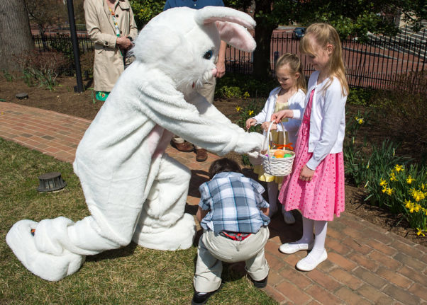 The Easter Bunny placing eggs in a girls basket at the annual Maryland House Easter egg hunt while another girl and boy look on. (Photo: Jay Baker/Maryland GovPics/Flickr)