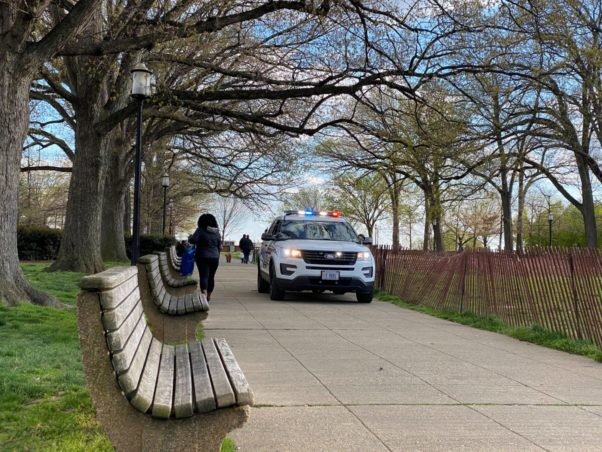 Polic car on a path by a bench in Meridian Hill Park. (Photo: Jacob Fenston/WAMU)