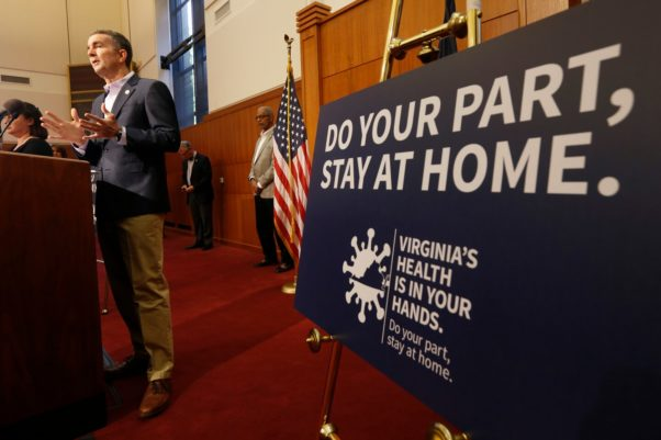 """Virginia Gov. Ralph Northam at a press conference in Richmond on April 8 with a sign to his left that reads """"Do Your Part, Stay at Home."""" (Photo: Steve Helber/AP)"""