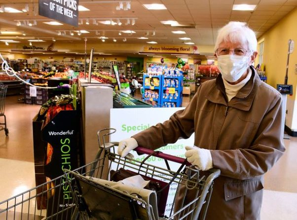 An elderly woman shopping in a grocery storey wearing a face mask and gloves. (Photo: Mike Orazzi/Flickr)