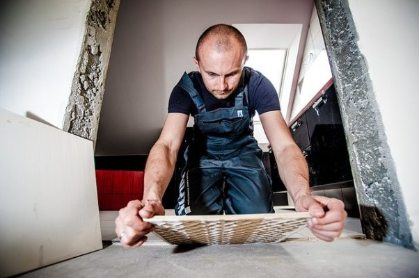 A man in overalls laying floor tile. (Photo: Michal Jarmoluk/Pixabay)