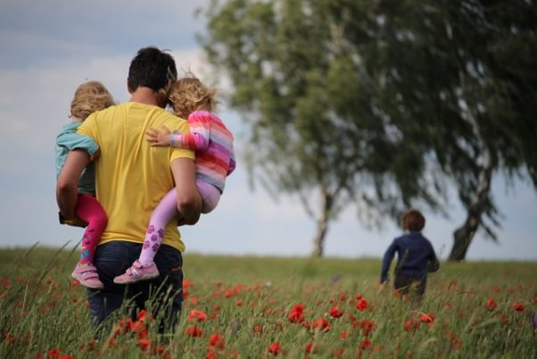 Man carrying two girls through a feild of red flowers. (Photo: Juliane Libermann/Unsplash)