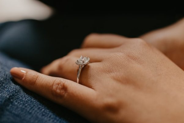 A woman's hand with an engagement ring on it. (Photo: Karina Thomason/Unsplash)