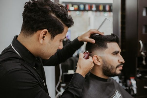 A barber cutting another man's hair. (Photo: Luis Quintero/Pexels)