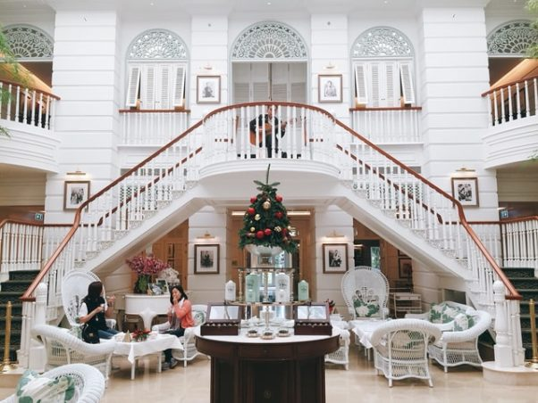 Interior photo of a white room with a double-sided stairway in the center with 2 women having tea. (Photo: Sidny See/Unsplash)
