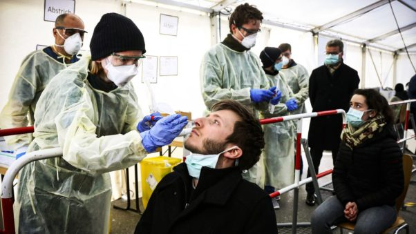 A man gets a nasal swab at a walk-through testing site set up in a tent. (Photo: Matthias Schrade/AP)