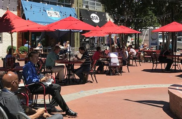 People eating at outdoor tables with red umbrellas in Bethesda. (Photo: Bethesda Urban Partnership)