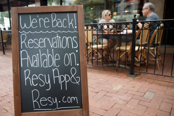 """People eat on the patio at the Carlyle restaurant in Shirlington on May 29, 2020 with a sign that says """"We're Back! Reservation available on Resy app & resy.com"""" (Photo: Shawn Thew/EPA-EFE-Shutterstock)"""