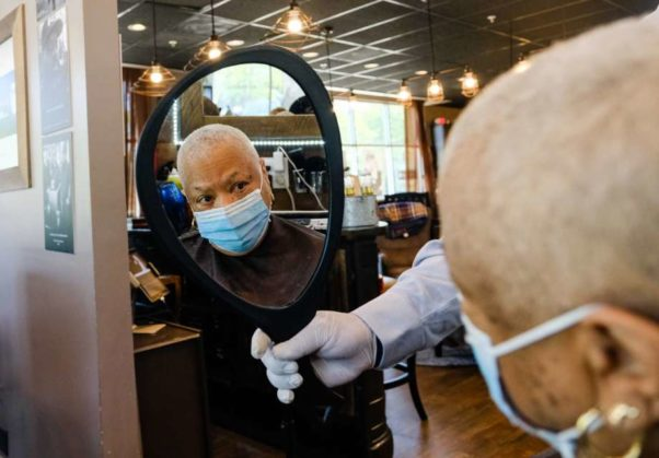 A woman looks at the back of her head in a mirror after getting a hair cut. (Photo: Michael A. McCoy/Washington Post)