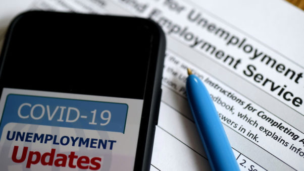 In this photo illustration, a COVID-19 Unemployment Assistance Updates logo is displayed on a smartphone on top of an application for unemployment benefits. (Photo: Olivier Douliery/AFP/Getty Images)
