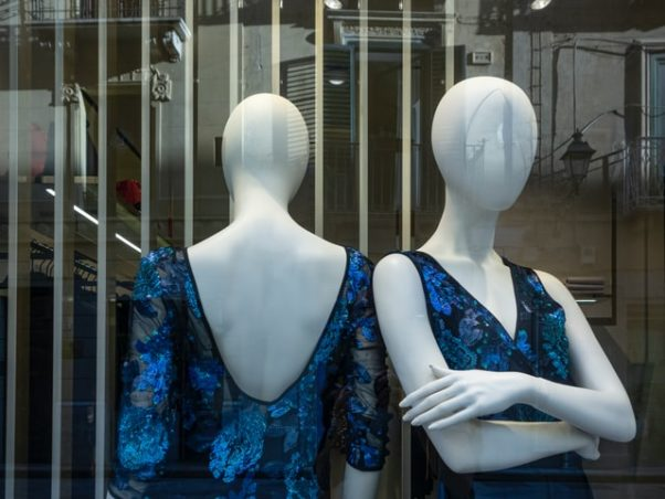 Two mannequins in a window wearing similar blue and black dresses. (Photo: Wolfgang Mennel/Unsplash)
