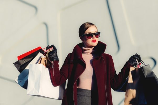 A woman in a burgandy coat and sunglasses holding shopping bags. (Photo: freestocks/Pexels)