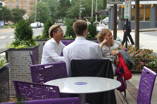 Two men and a woman sitting at a table talking in the Rosslyn Parklet. (Photo: Rosslyn BID)