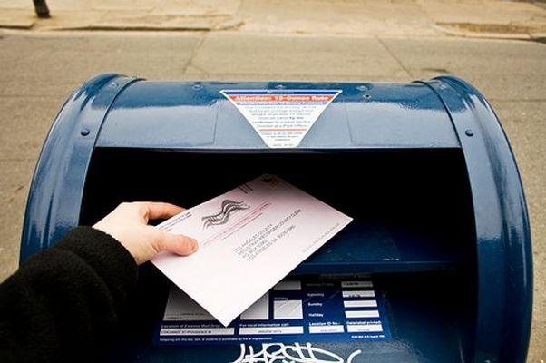 A person dropping an absentee ballot into a mailbox.