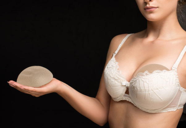 A woman wearing a bra holds a silicone breast implant. (Photo: American Society of Plastic Surgeons)