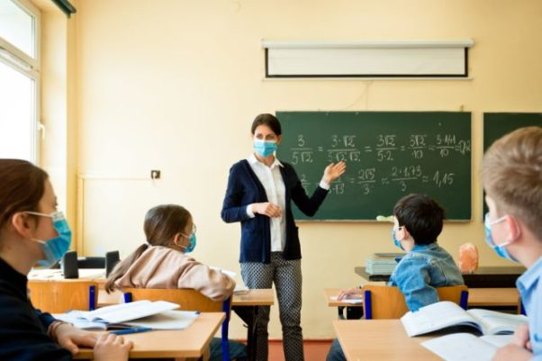A teacher wearing a face mask teaches math to students also wearing face masks. (Photo: Getty Images)
