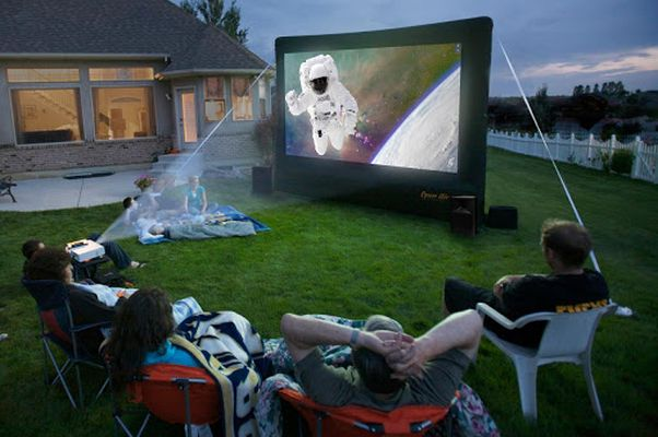 People watinging a movie on an outdoor movie screen set up in a backyard. (Photo: Ww85)