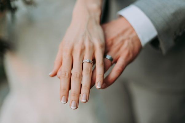A bride's hand on top of the groom's hand, both wearing wedding rings. (Photo: Samantha Gades/Unsplash)
