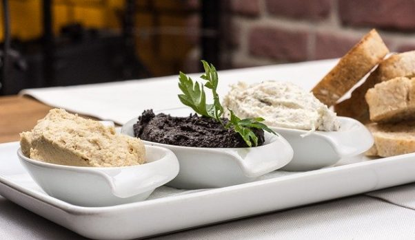 Three dips including hummus and olive paste in small bowls on a plate beside bread. (Photo: Christo Anestev/Pixabay)