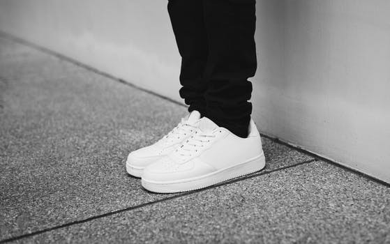 A persons legs dressed in black pants and white sneakers. (Photo: Rawpixel)