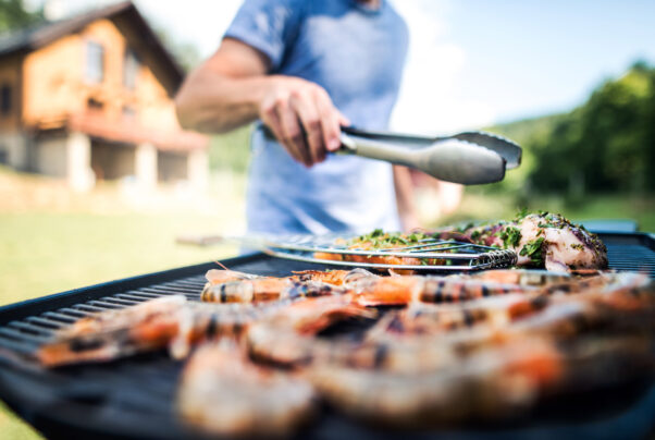 Unrecognizable man cooking seafood on a barbecue grill in the backyard on a sunny day. (Photo: Adobe Stock Images)