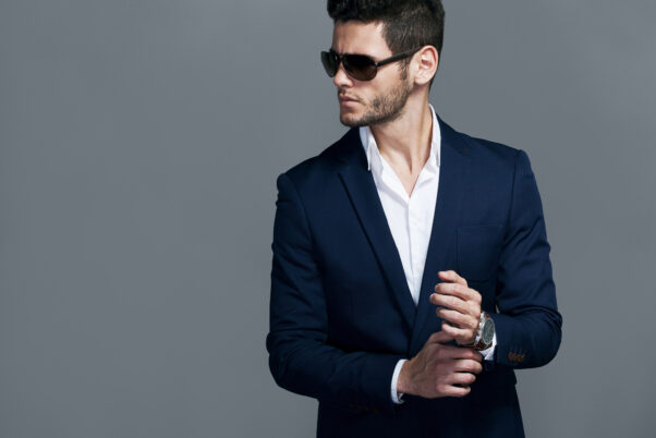 Elegant young handsome man wearing sunglasses and a suit without a tie. (Photo: Adobe Stock Photo)