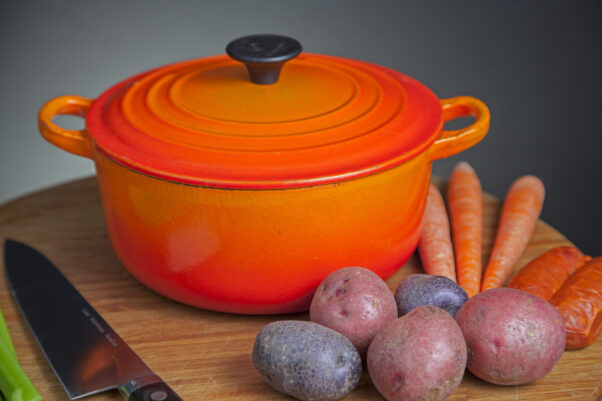 Orange enamel Dutch oven on cutting board with vegetables and cutlery on one side. (Photo: akatz66/Adobe Stock))