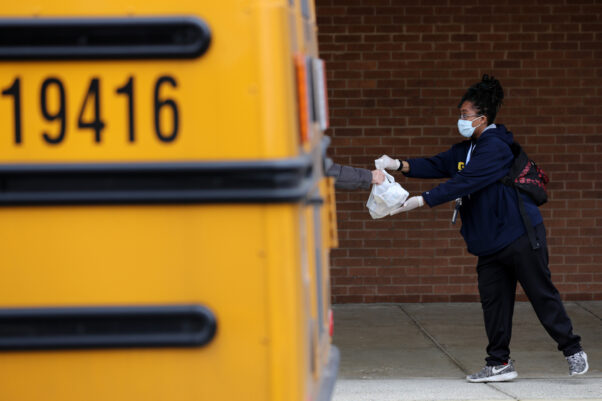 An MCPS worker hands a bag of food from beside a school bus to a girl wearing a backpack. (Photo: Chip Somodevilla/Getty Images)