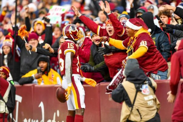 Fans in the stands give a Washington Football Team player high fives in 2019's game against the Dallas Cowboys. (Photo: Washington Football Team)
