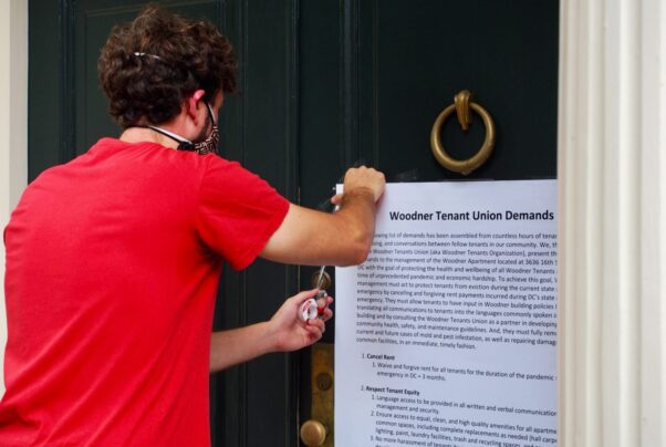 A Woodner tenant tapes a list of residents' demands to the front door of the building manager's house. (Photo: Gabe Bullard/WAMU)