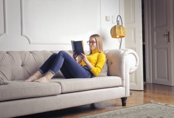 Woman in a yellow shirt and jeans lying on a couch reading a book. (Photo: Andrea Piacquadio/Pexels)