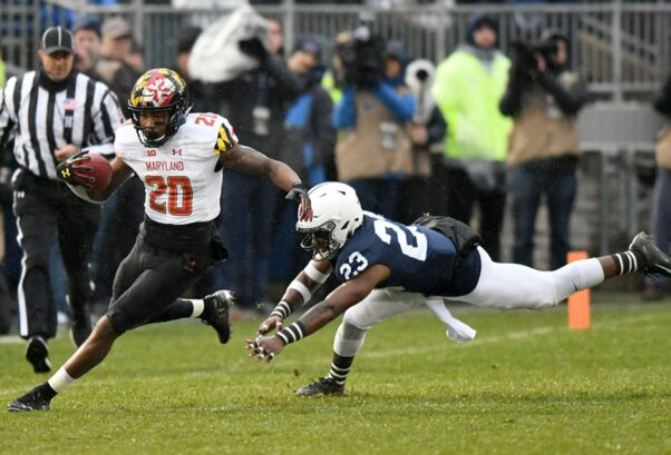 UMD's #20 carries the football down the field as the dodges a Penn State player. (Photo: University of Maryland)