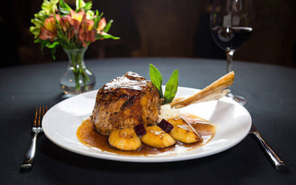 A fancy restaurant meal with a lambchop, mashed potatoes and mixed vegetables on a white plate with a glass of wine and clear vase with flowers nearby. (Photo: Christini's)
