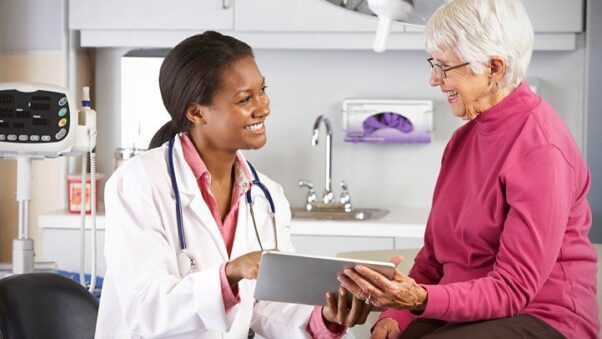 A black, female doctor showing an elderly female patient results on an electronic tablet. (Photo: Shutterstock)