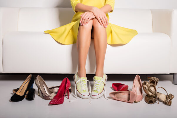 Woman in a yellow dress sitting on couch and trying on shoes. (Photo: Adobe Stock)