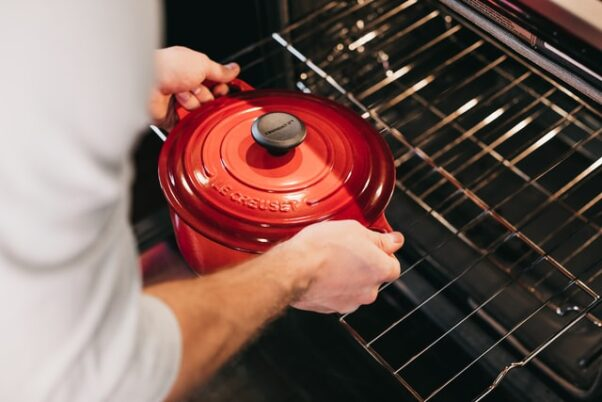 A man putting a red Dutch over pan into the overn. (Photo: Becca Tapert/Unsplash)