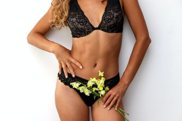 Torso of a woman in black lace bra and panties holding flowers. (Photo: Dainis Graveris/Unsplash)